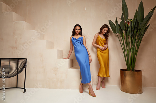Fényképezés Two pretty beautiful woman brunette hair natural makeup wear fashion clothes sexy silk long dress midi style date party walk sandals interior studio stairs flowerpot summer journey romantic friends