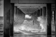 Below View Of Pier With Waves Splashing In Sea