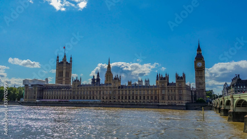 Fotografía Palace Of Westminster And Big Ben By Thames River Against Blue Sky