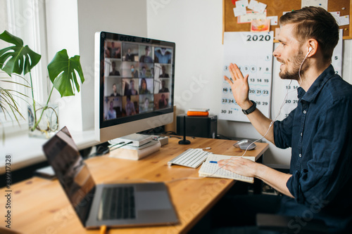 Foto Young man having Zoom video call via a computer in the home office