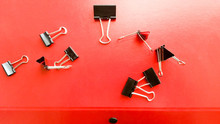 High Angle View Of Paper Clips On Red Surface