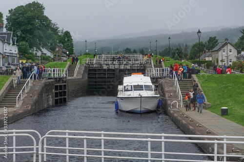 Fényképezés Fort Augustus, Scotland, UK: Crowds of people visit the Caledonian Canal locks at the south side of Loch Ness on a cloudy day