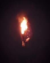 Man Holding Flaming Torch Against Black Background