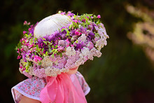 Adorable Little Girl In A Handmade Hat Decorated With Fresh Wildflowers.