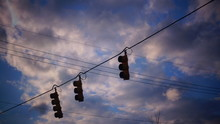 Low Angle View Of Railway Signal On Cable Against Cloudy Sky