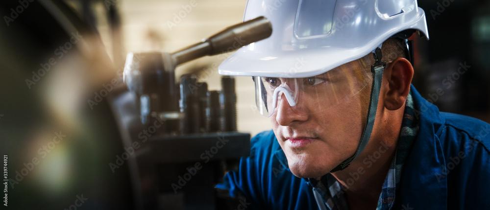 Fototapeta industrial background of caucasian mechanics engineer operating lathe machine for metalwork in metal work factory
