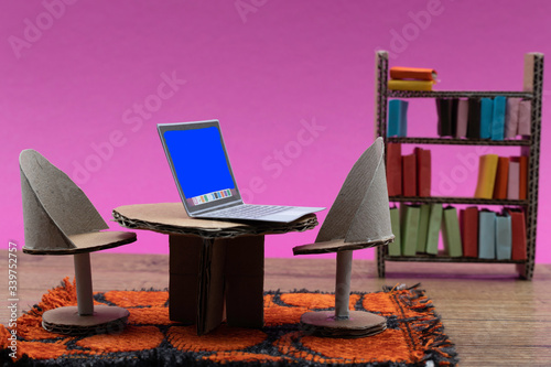 Fototapeta Working from home concept with cardboard furniture in a dollhouse living room