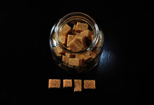 Brown Sugar Cubes With Glass Jar On Table