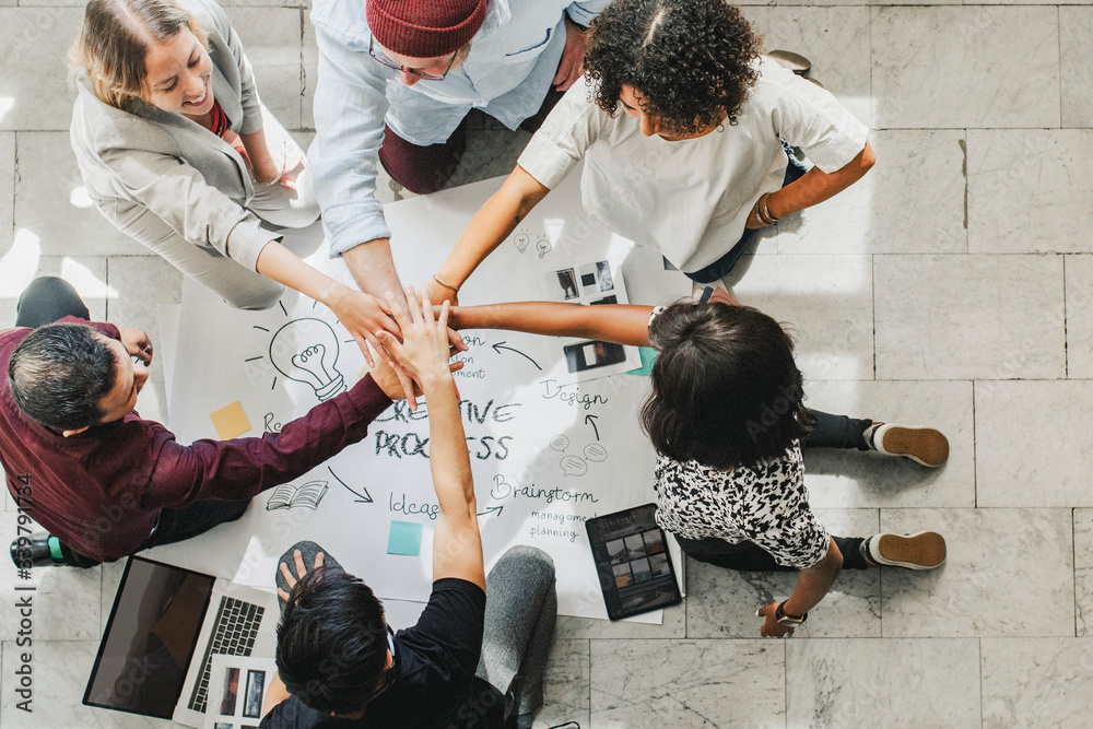 Fototapeta Diverse startup business team stacking hands