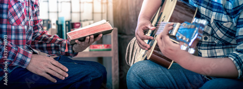 Worship God of two young christian sitting and sing a song, focus at hand, Christian worship concept Fototapet