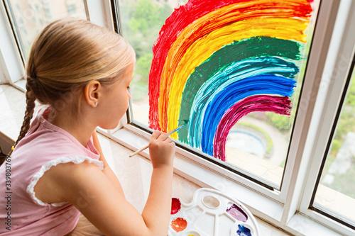 Fotografie, Obraz Kid painting rainbow during Covid-19 quarantine at home
