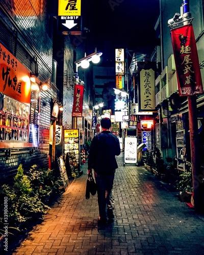 Obraz Rear View Of Man Walking On Footpath At Night - fototapety do salonu