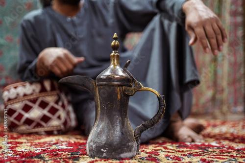 Closeup of traditional Arab teapot with Bedouin man wearing traditional clothes Canvas Print