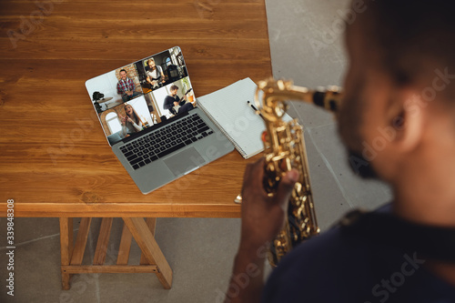 African-american musician playing saxophone during online concert at home isolated and quarantined Fototapeta