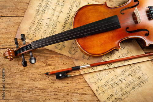Photo classic retro violin music string instrumt with old music note sheet paper old oak wood wooden background