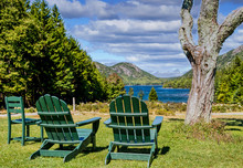 Two Green Adirondack Chairs In A Park Overlooking A Blue Lake