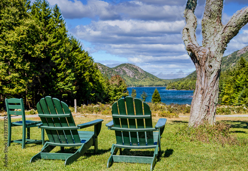 Two green adirondack chairs in a park overlooking a blue lake Wallpaper Mural