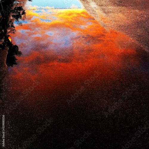 Canvas Print High Angle View Of Clouds Reflection In Puddle On Street During Sunset