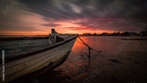 Boat Moored At Shore Against Cloudy Sky During Sunset