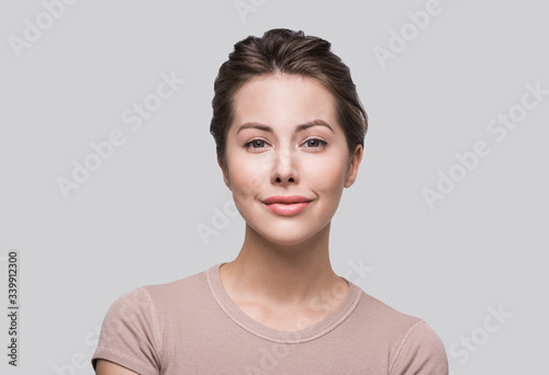 Beautiful young woman studio closeup portrait. Smiling girl looking at camera isolated on gray background. Model with perfect clean skin. Beauty, makeup, healthy lifestyle and skin care concept