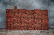 View Of Red Bricks Stacked Against Grey Concrete Wall