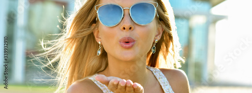 Outdoor fashion portrait of young pretty   blond woman in sunny day on street Fototapet