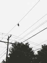 Low Angle View Of Shoes Hanging On Telephone Lines