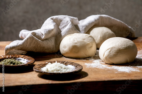 Fototapeta Dough for italian pizza napolitana cooking. Three balls of fresh homemade wheat dough and ingredients in ceramic plates above on wooden kitchen table. Home baking. obraz