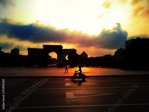 Photo Silhouette Woman Riding Motor Scooter On Road Against Triumphal Arch