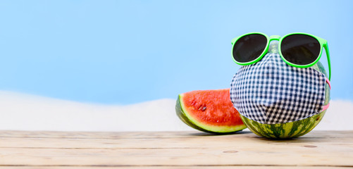 Creative minimal summer beach holiday with fresh watermelon. Wearing sunglasses and face mask because social distancing and Covid-19.