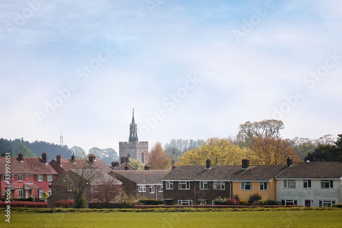 An old village church with modern housing obscuring it´s full aspect in the fore Canvas Print