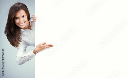 Fototapeta Happy young woman showing blank sign board with copy space for some slogan, text or imaginary. Business ad concept. Multiracial Asian Chinese / Caucasian model over grey background. obraz