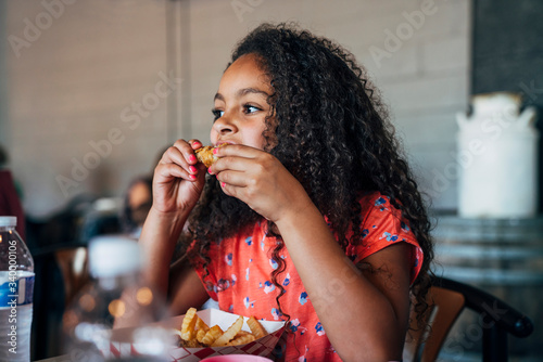 Girl eating chicken wings and french fries take out with hands