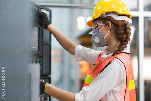 Papel de parede Female Engineer wear face mask with safety vest and yellow helmet operating cont