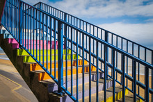 Concrete Steps Painted Bright Rainbow Colours With A Blue Railing Infront Of A Beach With Sand. The Sky Is Blue With White Clouds.