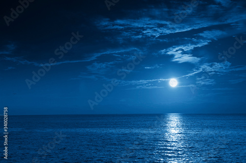 Valokuva This photo illustration of a deep blue moonlit ocean and sky at night  would make a great travel background for any travel or vacation purpose