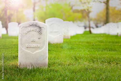 Valokuvatapetti Tombstone of unknown soldier on the cemetery grass ground with other graves on b