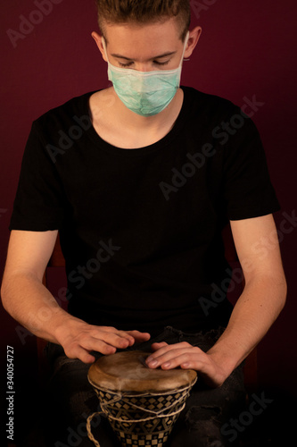 Canvas Print Coronavirus, quarantine at home, playing drums in protection mask