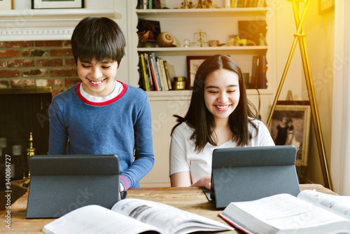 Fototapeta Siblings do their school work from home during social distancing - Homeschool - Happy - Tablets obraz