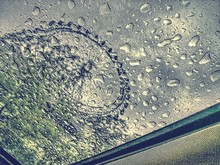 Low Angle View Of Ferris Wheel Seen Through Wet Window