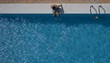Aerial shot a boy sitting on the edge of a pool with clear blue water