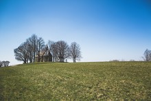 Shot Of A Church Surrounded By Bare Trees On A Green Hill, Bright Blue Sky Above