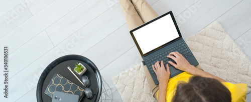 Fototapeta Top view of female freelancer sitting on floor near sofa at home and working on mockup laptop computer. Woman typing on laptop stay home. Quarantine concept work online obraz