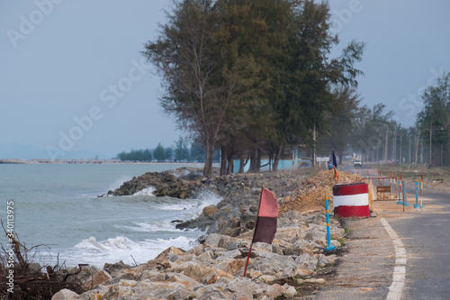 Photo Waves of sea erode the road.