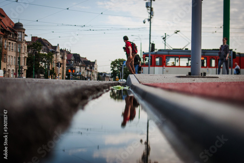 Reflection Of People In Puddle On Street Against Sky Wallpaper Mural