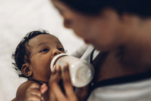 Portrait Of Enjoy Happy Love Family African American Mother Playing With Adorable Little African American Baby.Mom Feeding Bottle Of Milk To Baby Cute Son In A White  Bedroom.Love Of Black Family