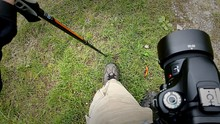 Low Section Of Man Standing On Grassy Field With Camera