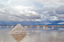 Salt Mountains In Uyuni Salt Flat (Bolivia), The Biggest Salar In The World Covered With Water And Reflecting Like A Mirror The Sky During A Bright Day With Blue Sky And White Clouds.