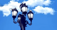 Low Angle View Of Birds Perching On Lamp Post Against Sky
