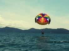 Friends Parasailing Over Sea Against Sky